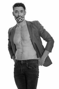 Porträt des gutaussehenden mannes, der maske trägt, um vor der covid-19-infektion zu schützen, die in schwarzweiss geschossen wird