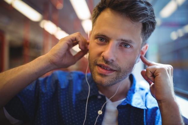 Porträt des gutaussehenden mannes, der musik hört