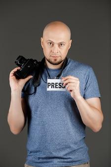 Porträt des gutaussehenden mannes im grauen hemd mit fotokamera und druckabzeichen, das über dunkler wand aufwirft