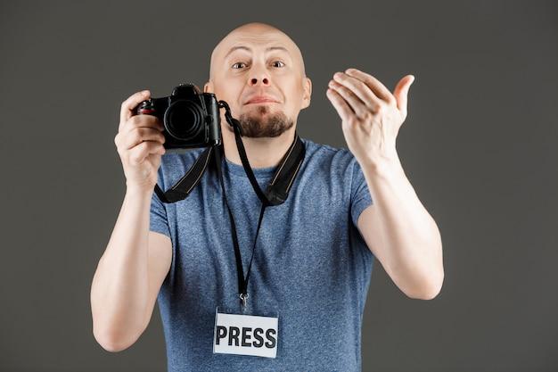 Porträt des gutaussehenden mannes im grauen hemd mit fotokamera und druckabzeichen, die bilder über dunkler wand machen