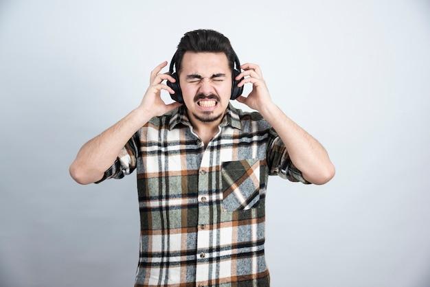 Porträt des gutaussehenden mannes in den kopfhörern, der lied auf weißer wand hört.