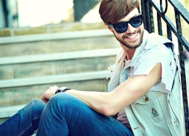 Porträt des gutaussehenden mannes in der stilvollen hipster-kleidung. attraktiver typ, der auf der straße aufwirft
