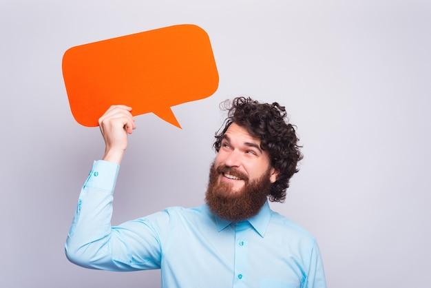 Porträt des gutaussehenden mannes mit bart, der rote leere sprechblase hält und betrachtet