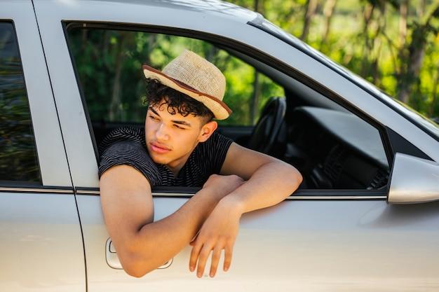Porträt des gutaussehenden mannes schauend weg von autofenster