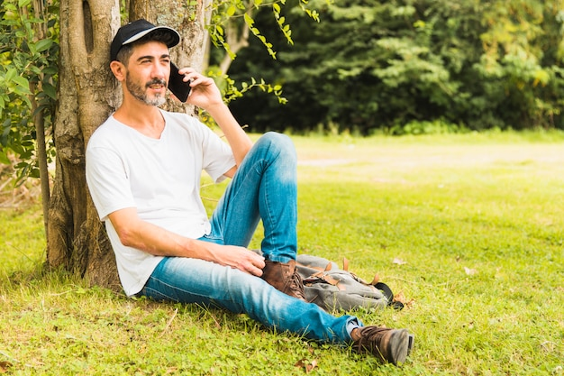 Porträt des gutaussehenden mannes sitzend unter dem baum, der am handy im park spricht