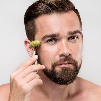 Porträt des gutaussehenden mannes unter verwendung einer gesichtsrolle