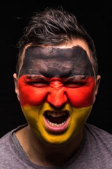 Porträt des gutaussehenden manngesichtsanhängerfans der deutschen nationalmannschaft mit gemaltem flaggengesicht lokalisiert auf schwarzem hintergrund. fans emotionen.