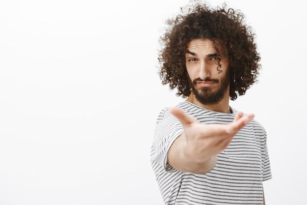 Porträt des gutaussehenden selbstbewussten machomannes mit bart und lockigem haar, hand in richtung ziehend