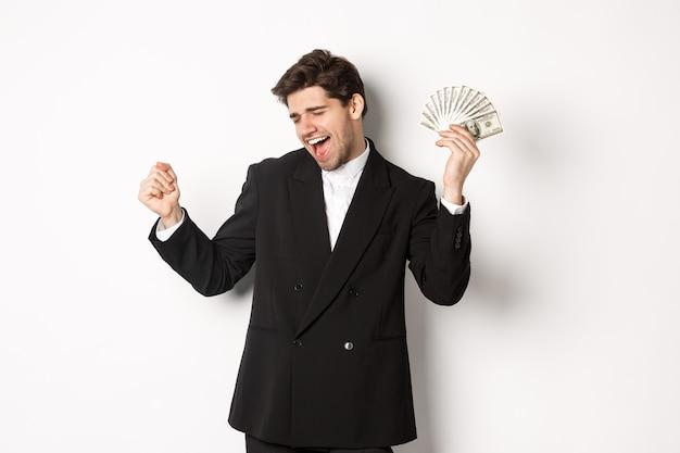 Porträt des gutaussehenden und erfolgreichen geschäftsmannes im anzug, tanzend mit geld, stehend vor weißem hintergrund.