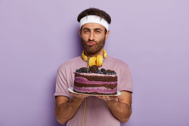 Porträt des gutaussehenden unrasierten mannes hält köstlichen kuchen auf teller, gekleidet in freizeitkleidung, hat guten willen, keine dessertständer gegen lila wand zu essen, genießt guten geschmack. männchen mit süßem gericht