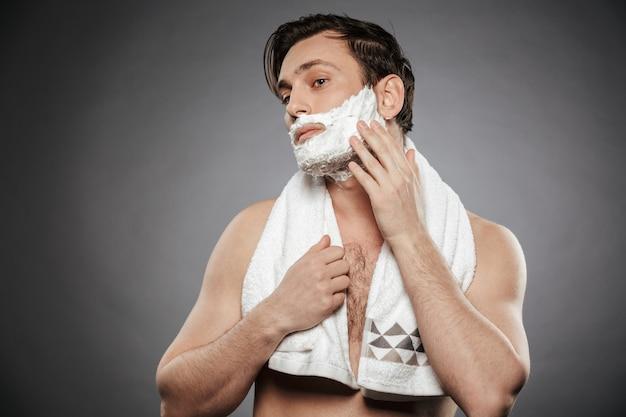 Porträt des halbnackten erwachsenen kerls, der rasierschaum auf gesicht mit handtuch auf seinem hals lokalisiert über graue wand setzt