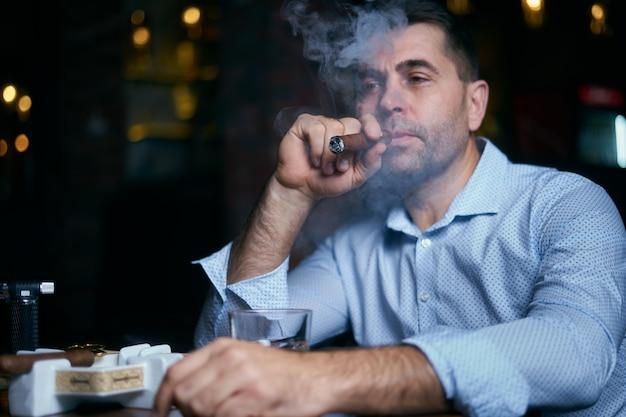 Porträt des hansome mannes, der zigarre in einer loungebar raucht