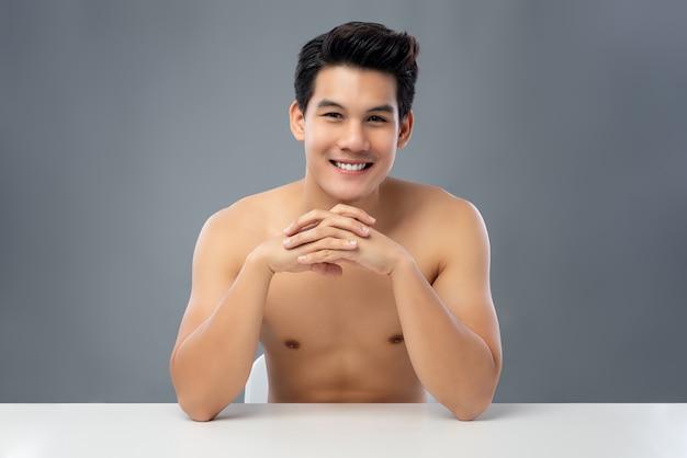 Porträt des hemdlosen hübschen lächelnden jungen asiatischen mannes, der mit handverschluss sitzt