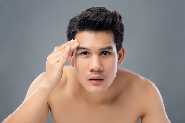 Porträt des hemdlosen jungen hübschen asiatischen mannes, der seine gesichtshaut überprüft