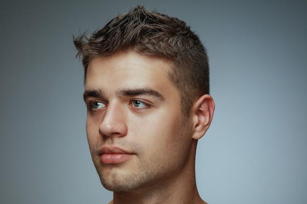 Porträt des hemdlosen jungen mannes lokalisiert auf grauem studiohintergrund. kaukasisches gesundes männliches modell, das seite betrachtet und aufwirft. konzept der gesundheit und schönheit von männern, selbstpflege, körper- und hautpflege.
