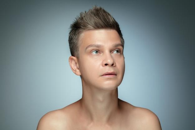 Porträt des hemdlosen jungen mannes lokalisiert auf grauer studiowand.