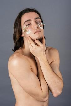 Porträt des hemdlosen mannes mit blumen auf seinem gesicht