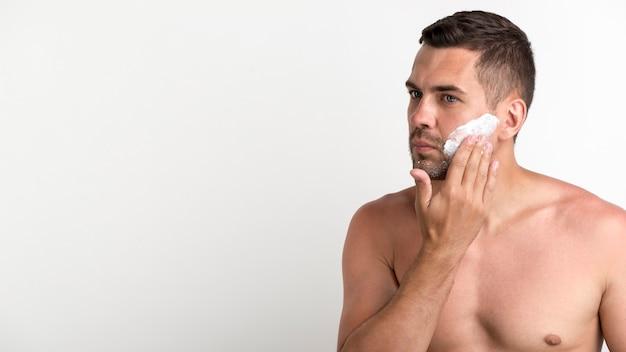 Porträt des hemdlosen mannes schaum beim rasieren anwendend