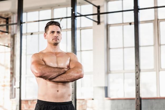 Porträt des hemdlosen muskulösen mannes mit den armen gekreuzt
