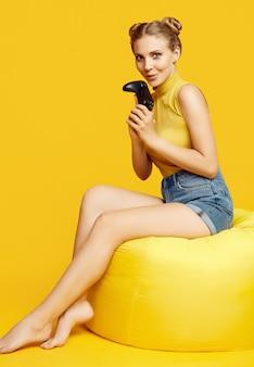 Porträt des herrlichen glücklichen blonden spielermädchens, das videospiele mit joystick auf gelb im studio spielt
