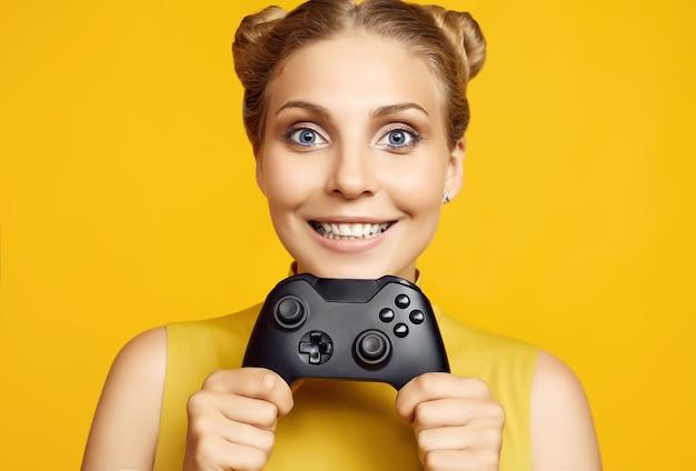 Porträt des herrlichen glücklichen blonden spielermädchens, das videospiele mit joystick auf gelber wand im studio spielt