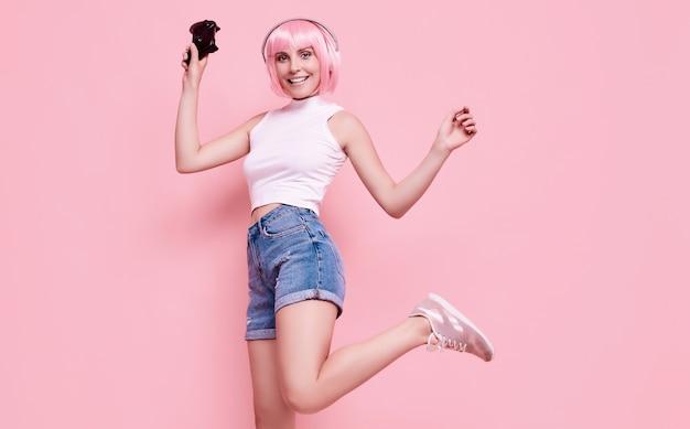 Porträt des herrlichen glücklichen spielermädchens mit rosa haaren, die videospiele mit joystick auf bunt im studio spielen
