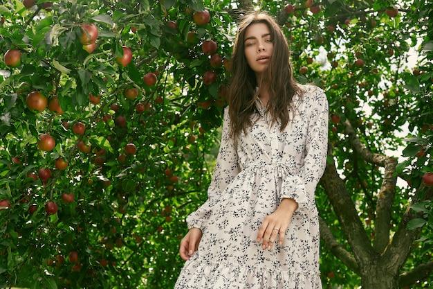 Porträt des herrlichen klassischen kleides der brunettefrau in mode, das unter apfelbäumen aufwirft