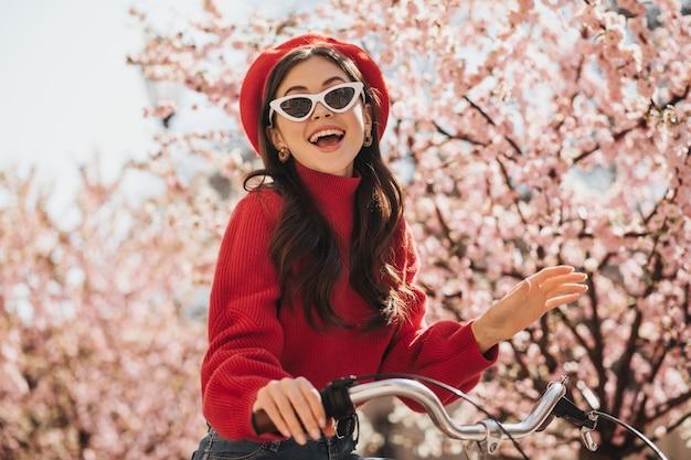 Porträt des herrlichen mädchens im roten outfit und in der sonnenbrille auf hintergrund der sakura. fröhliche frau in kaschmirpullover und baskenmütze lächelnd und fahrrad fahrend