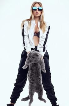 Porträt des herrlichen modellmädchens in einem trainingsanzug, der mit einer fetten stammbaumkatze lokalisiert aufwirft