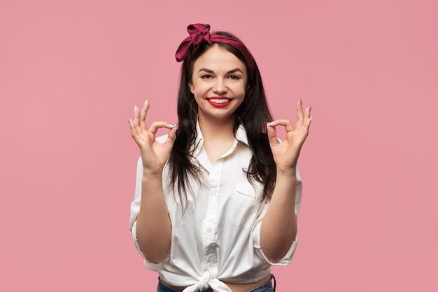 Porträt des herrlichen pin-up-mädchens mit weißem hemd und rotem kopftuch, das mit beiden händen eine zustimmende geste macht