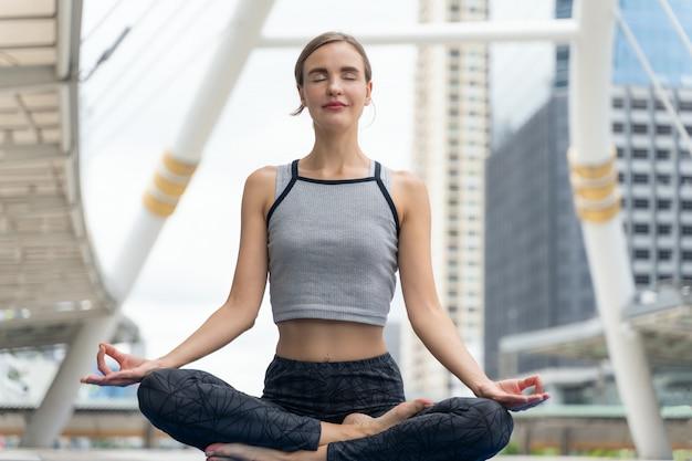 Porträt des herrlichen übenden yoga der jungen frau im freien in der stadt. schönheitspraxisyoga und -meditation für entspannen sich in der klasse. gelassenheit und entspannen sich