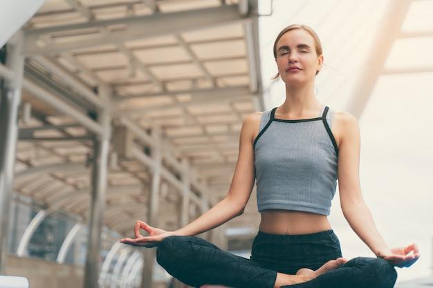 Porträt des herrlichen übenden yoga der jungen frau im freien in der stadt.