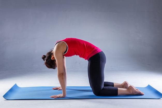 Porträt des herrlichen übenden yoga der jungen frau im studio mit auf dunklem hintergrund