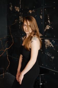 Porträt des herrlichen weiblichen brünetten modells, das in der weißen modekleidung im studio aufwirft
