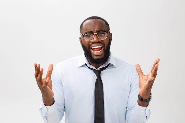 Porträt des hoffnungslosen gestörten schwarzen mannes, der in der raserei und in der wut schreit, die heraus sein haar beim gefühl mit etwas wütend und wütend sich fühlen