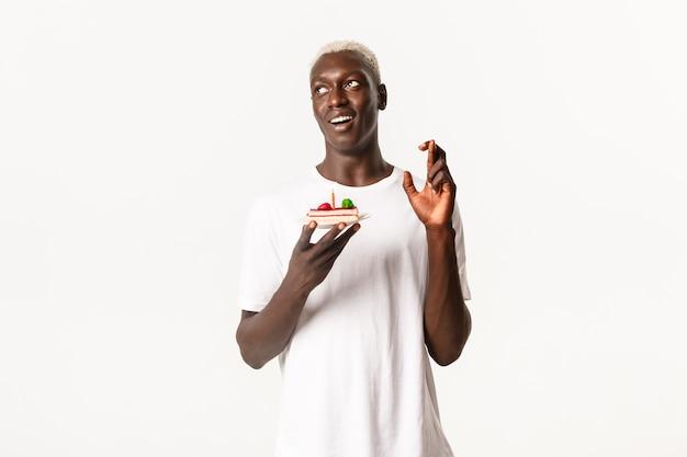 Porträt des hoffnungsvollen attraktiven schwarzen kerls, der geburtstag feiert, wunsch macht und b-tageskuchen hält, daumen drücken für traum wahr wird