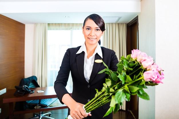 Porträt des hotelmanagers, der blumenstrauß hält