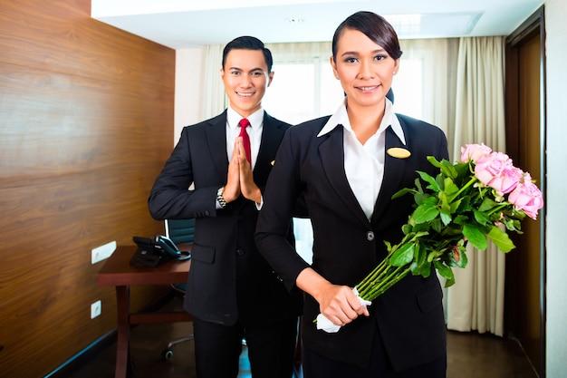 Porträt des hotelpersonals, das mit blumen grüßt