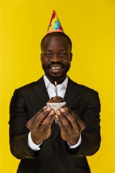 Porträt des hübschen afrikanischen mannes, der einen kuchen mit einem fokus auf dem kuchen hält