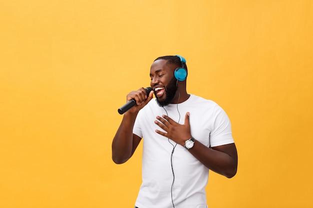 Porträt des hübschen afrikanischen mannes des netten positiven chic, der mikrofon hält und kopfhörer hat