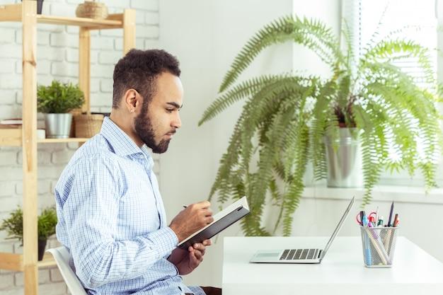 Porträt des hübschen afrikanischen schwarzen jungen geschäftsmannes, der an laptop im büro arbeitet