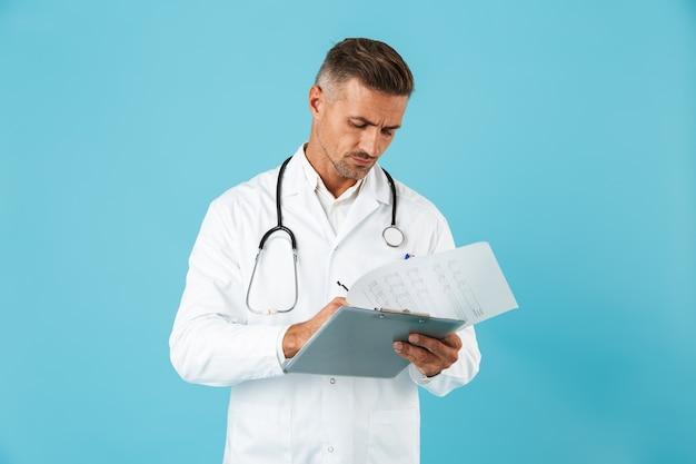 Porträt des hübschen arztes mit stethoskop, das gesundheitskarte hält, lokalisiert über blauer wand