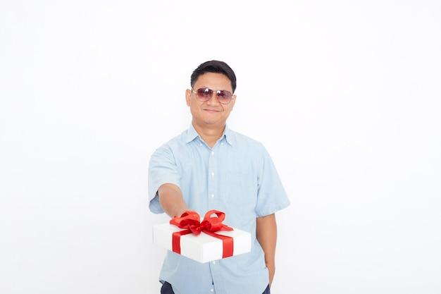 Porträt des hübschen asiatischen mannes, der geschenkbox hält