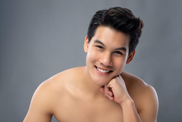 Porträt des hübschen asiatischen mannes, der kamera mit der hand auf kinn betrachtet