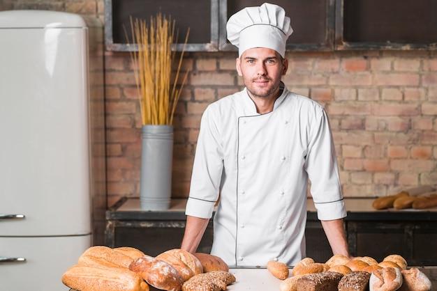 Porträt des hübschen bäckers an der bäckerei mit broten in der bäckerei
