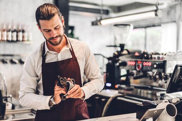 Porträt des hübschen bärtigen barista-mann-kleinunternehmers, der mit laptop-computer hinter der thekenbar in einem café arbeitet