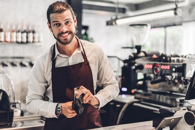 Porträt des hübschen bärtigen barista-mannes kleinunternehmer, der hinter der thekenbar in einem café arbeitet