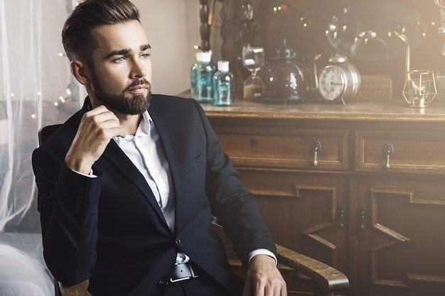 Porträt des hübschen bärtigen mannes, der schwarzen klassischen anzug trägt