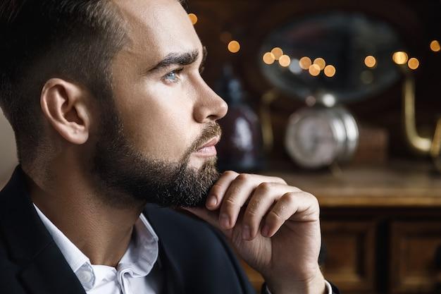 Porträt des hübschen bärtigen mannes, der schwarzen klassischen anzug trägt Premium Fotos