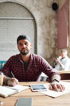 Porträt des hübschen bärtigen mannes in der ballkappe, die am tisch sitzt und notizen im planer macht, während er über reise nachdenkt
